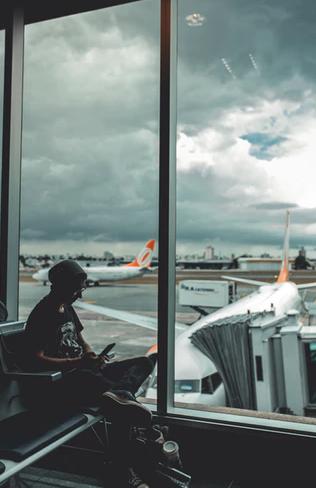 mulher em aeroporto vendo celular